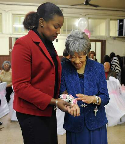 Sylvia Hill, known as Mother Hill, right, looks at her new corsage while she holds the hand of her great niece Naomi Clarke of Albany as members of Wilborn Temple Church of God in Christ celebrate her 100th birthday at Wilborn Temple on Wednesday, Nov. 11, 2015 in Albany, N.Y.  (Lori Van Buren / Times Union) Photo: Lori Van Buren / 00034206A