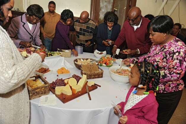 People help themselves to food as more than 100 members of Wilborn Temple Church of God in Christ celebrate the 100th birthday of Sylvia Hill, known as Mother Hill, at Wilborn Temple on Wednesday, Nov. 11, 2015 in Albany, N.Y.  (Lori Van Buren / Times Union) Photo: Lori Van Buren / 00034206A