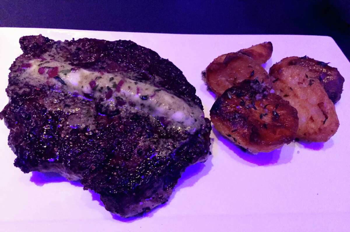 Cast-iron seared 14-ounce center-cut rib-eye with herb butter and crisp yellow potatoes confit