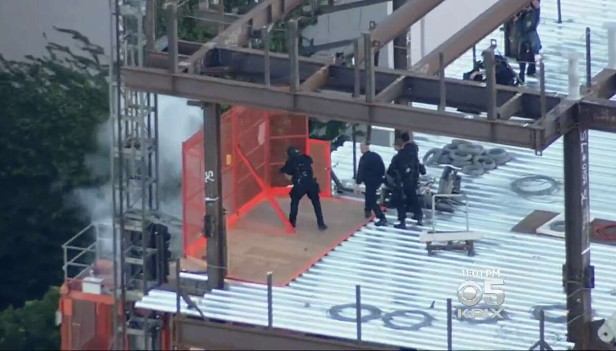 San Francisco Police release a flash bomb grenade at an elevator shaft where the shooter was perched.