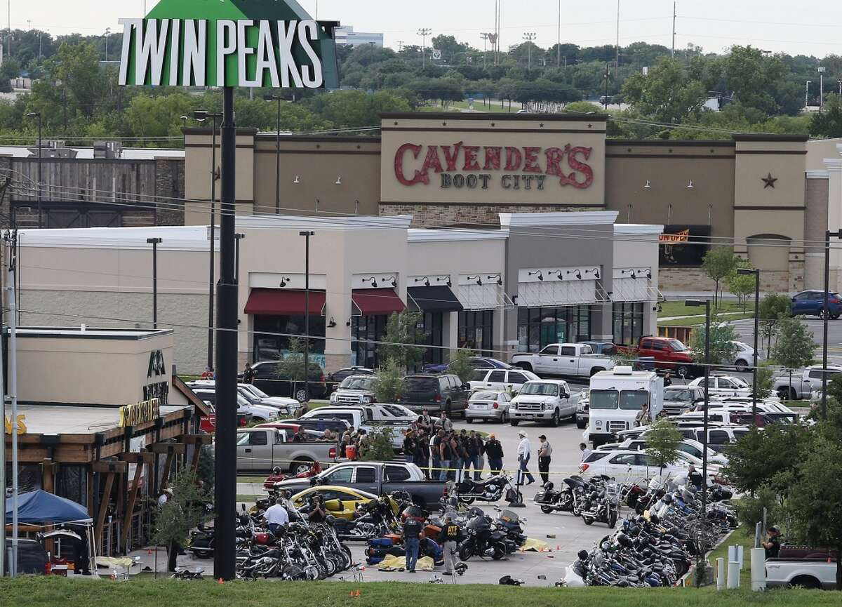 In this May 17, 2015 file photo, authorities investigate a shooting in the parking lot of Twin Peaks restaurant in Waco, Texas. The family of a biker slain in a shootout outside the Waco restaurant has sued the restaurant's parent company alleging negligence, according to a lawsuit filed Wednesday, July 8, 2015, in Dallas County. (AP Photo/Jerry Larson, File)