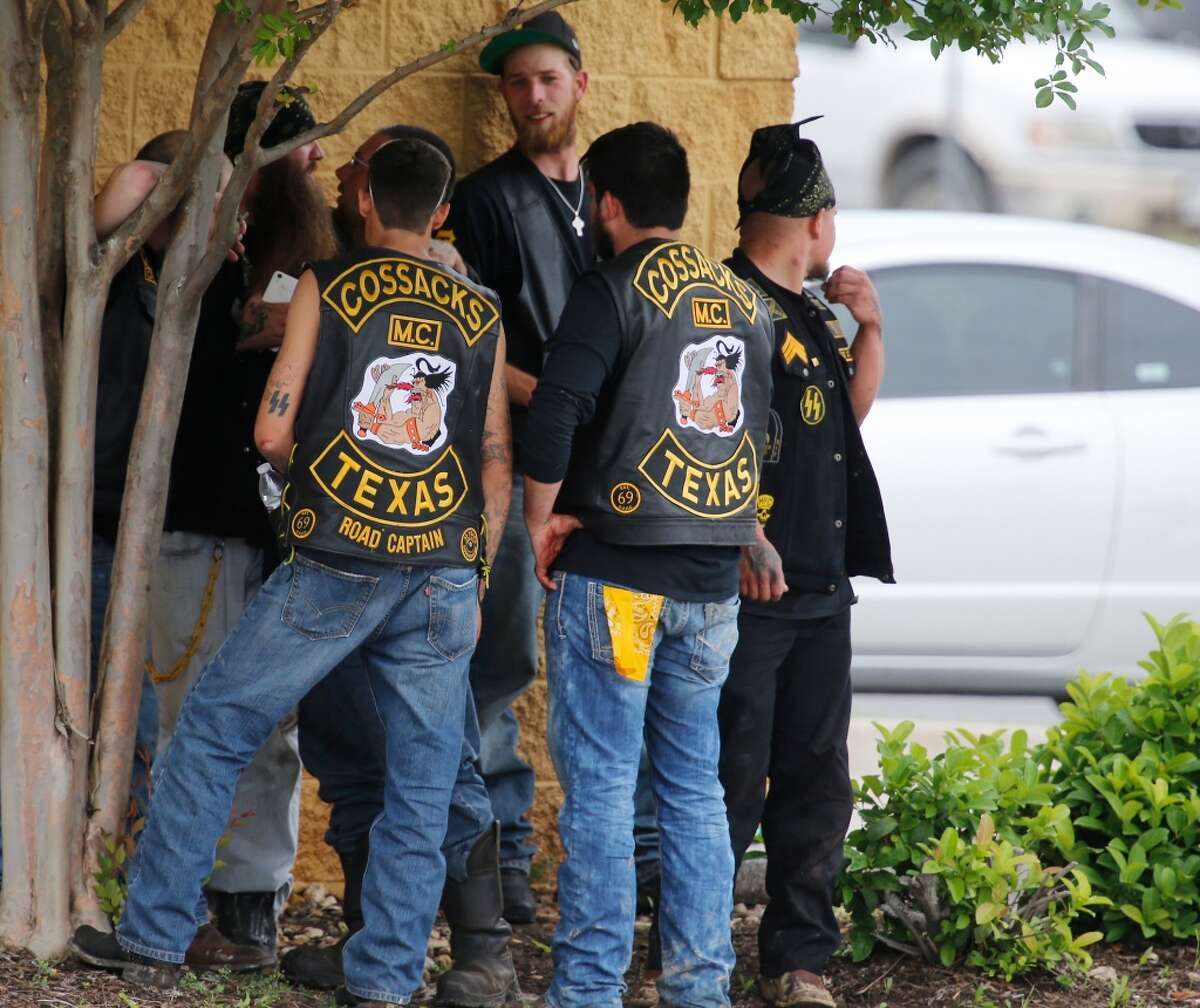 Bikers congregate against a wall while authorities investigate a Twin Peaks restaurant Sunday, May 17, 2015, in Waco, Texas. Waco Police Sgt. W. Patrick Swanton told KWTX-TV there were