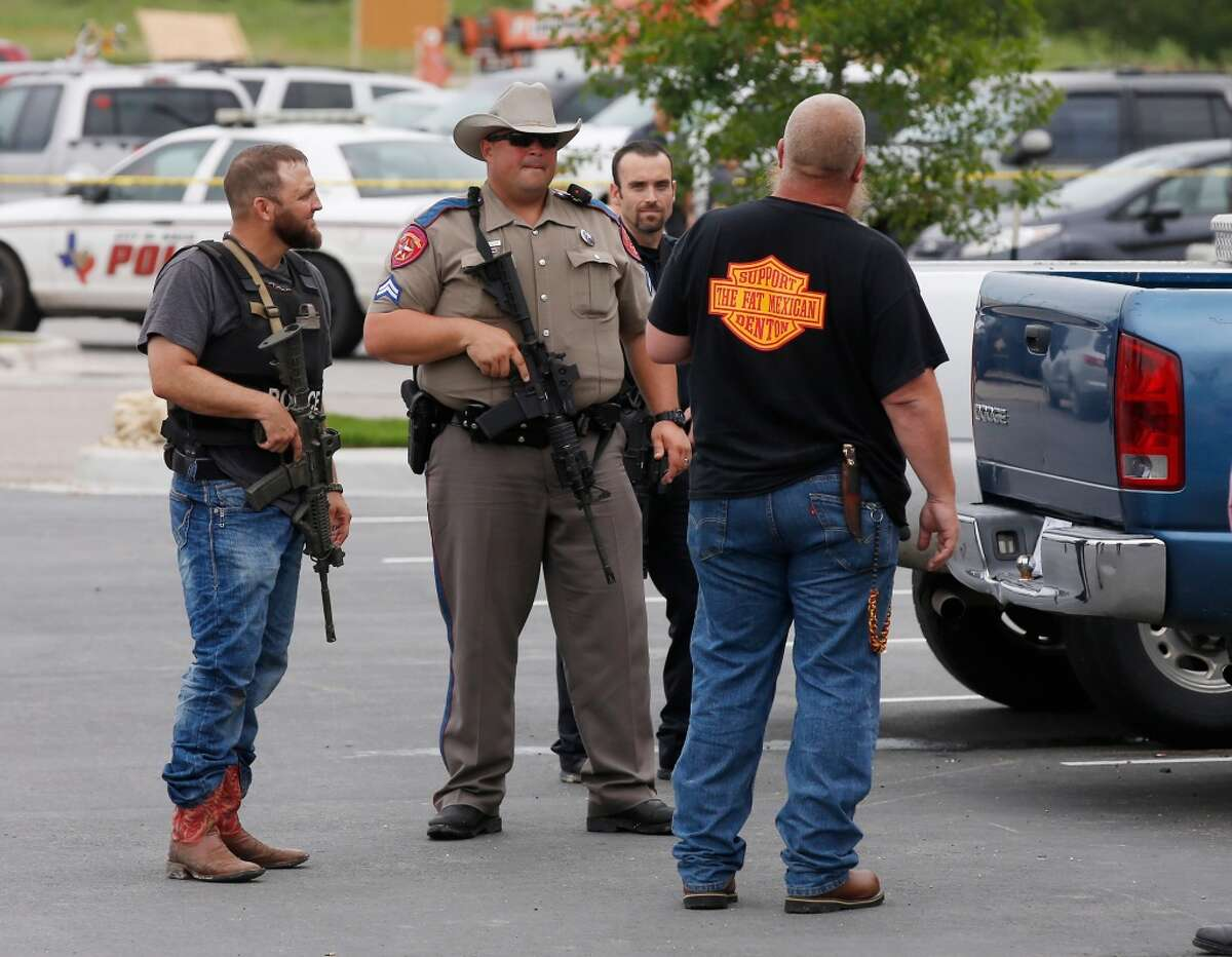 Law enforcement officers talk to a man near the parking lot of a Twin Peaks Restaurant Sunday, May 17, 2015, in Waco, Texas, after a shooting involving rival biker gangs. Waco police Sgt. W. Patrick Swanton told KWTX-TV there were ?'multiple victims?
