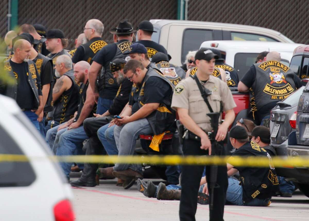 A McLennan County deputy stands guard near a group of bikers in the parking lot of a Twin Peaks restaurant Sunday, May 17, 2015, in Waco, Texas. Waco Police Sgt. W. Patrick Swanton told KWTX-TV there were