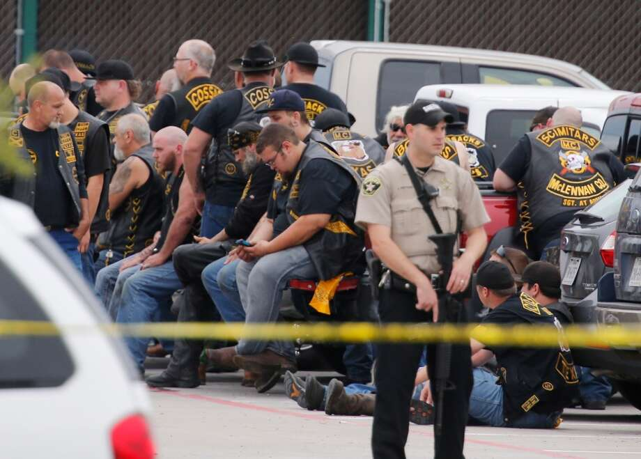 "A McLennan County deputy stands guard near a group of bikers in the parking lot of a Twin Peaks restaurant Sunday, May 17, 2015, in Waco, Texas. Waco Police Sgt. W. Patrick Swanton told KWTX-TV there were ""multiple victims"" after gunfire erupted between rival biker gangs at the restaurant. (Rod Aydelotte/Waco Tribune-Herald via AP) Photo: Rod Aydelotte, AP"