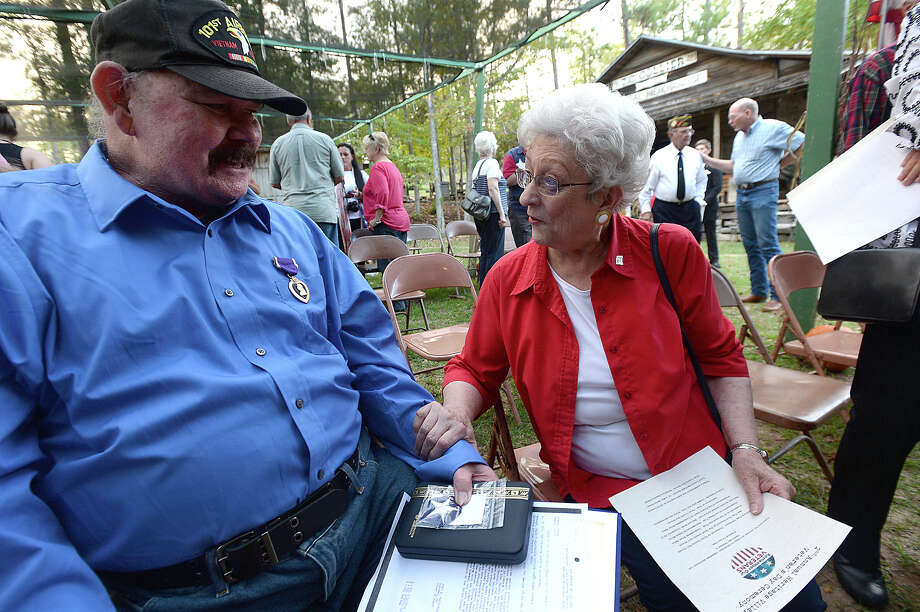 Vietnam veteran Craig Metcalf is congratulated by Mary Moye from the Tyler County Veterans Service Office after receiving a Purple Heart for heroic actions performed while serving in Vietnam in 1969 during a Veteran's Day ceremony held at Heritage Village in Woodville Wednesday. Congressman Brian Babin and State Representative James White joined in honoring veterans at the event.  Photo taken Wednesday, November 11, 2015  Kim Brent/The Enterprise Photo: Kim Brent / Beaumont Enterprise