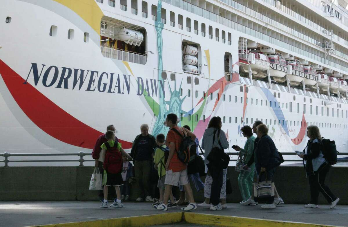 People stand with their luggage on Pier 88 in New York where passengers have just disembarked from the Norwegian Dawn cruise ship Monday, April 18, 2005. The ship was damaged by a freak seven-story wave on Saturday morning, April 16, while returning to New York from the Bahamas. (AP Photo/Tina Fineberg).