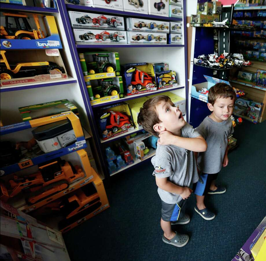 North Massey, 3, left, and his brother Miles, 2, check the shelves at Toys To Love. Below: A remote control R2-D2.  Photo: Karen Warren, Staff / © 2015 Houston Chronicle