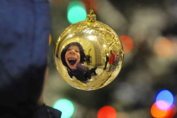 Bear Riversong, 7, checks out his reflection in a Christmas ornament at Albany City Hall in Albany on Monday, Dec. 6, 2010. (Paul Buckowski / Times Union) ORG XMIT: MER2015111212451907