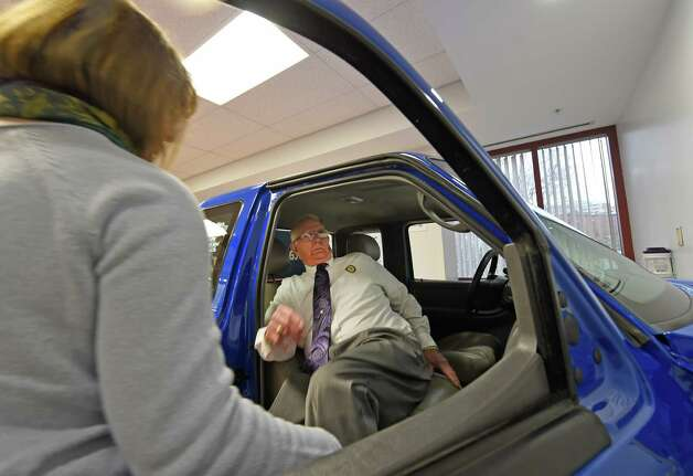 Terry Phillips demonstrates, from personal experience, how to enter and exit a vehicle after hip replacement surgery at Sunnyview Rehabilitation Hospital's new patient transfer vehicle specially made locally, and donated for the use with patients in therapy, Thursday Nov. 12, 2015 in Schenectady, N.Y.  The new therapy car allows therapists to help patients relearn and practice the critical skill of independently entering and exiting a vehicle.  (Skip Dickstein/Times Union) Photo: SKIP DICKSTEIN / 00034189A
