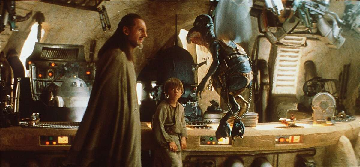 Jedi Master Qui-Gon Jinn (Liam Neeson) talks to junk dealer Watto about buying an uncommon spacecraft part as young Anakin Skywalker (Jake Lloyd) looks on in