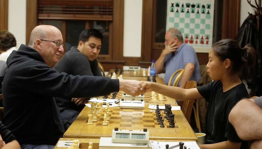 International Master Elliott Winslow (l to r), of Alameda, and Enkhjin Gomboluudev, 12, of El Sobrante, shake hands at the start of their game. Photo: Lea Suzuki, The Chronicle