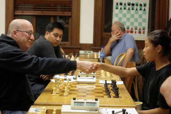 International Master Elliot Winslow (l to r), of Alameda, and Enkhjin Gomboluudev, 12, of El Sobrante shake hands at the start of their game in the Mechanics' Institute Chess Room  on Tuesday, November 3,  2015 in San Francisco, Calif.