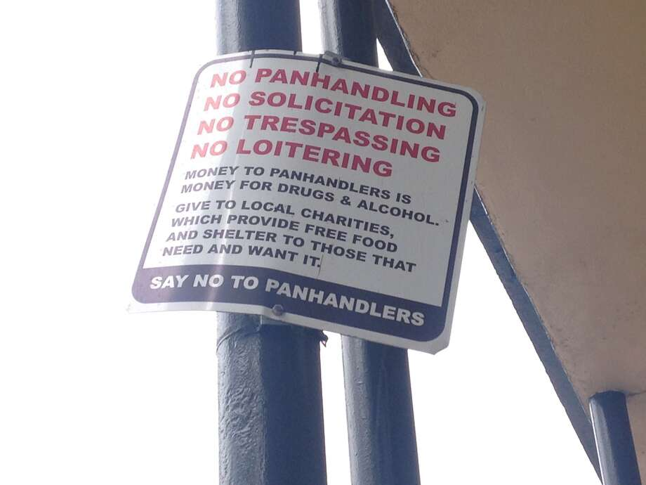 "The signs posted in the 400 block of Travis Street don't just prohibit panhandling, solicitation, trespassing and loitering, but go on to say ""money to panhandling is money for drugs and alcohol."""