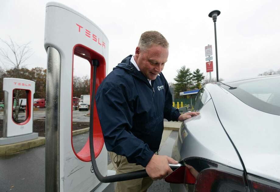 Kenny Horton, of Guilford, charges his Tesla electric vehicle Thursday, Nov. 12, 2015, at the Milford Service Area off of I-95 southbound, while he stops for coffee. Photo: Autumn Driscoll, Hearst Connecticut Media / Connecticut Post