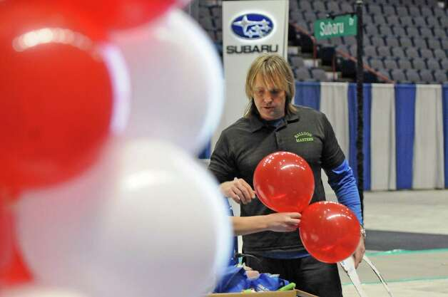 Chris Potts, right, and Stephanie Swald with Balloon Masters work on a balloon display for the Toyota booth in preparation for the Albany Auto Show at the Times Union Center on Thursday Nov.12, 2015 in Albany, N.Y. The show at the Times Union Center runs Nov. 13-15. (Michael P. Farrell/Times Union) Photo: Michael P. Farrell / 00034049A