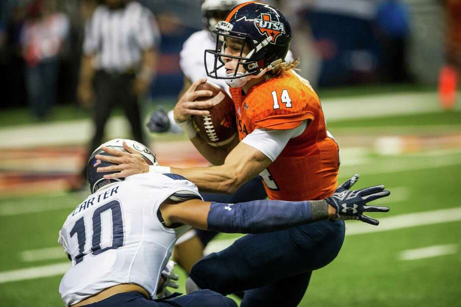 UTSA quarterback Dalton Sturm tries to run over Old Dominion's Sean Carter during their game at the Alamodome in San Antonio on Nov. 7, 2015. Photo: Matthew Busch /For The Express-News / © Matthew Busch 2015