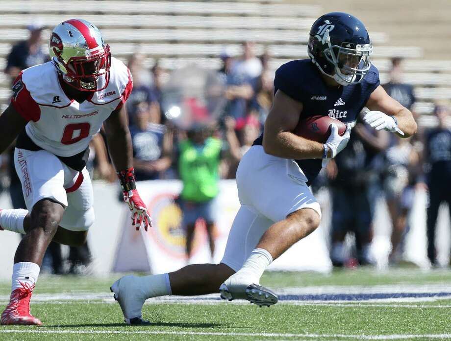 Rice's Luke Turner (35) runs for extra yards past WKU's Derek Brown in the first quarter. Photos of Rice University football game against Western Kentucky University at Rice Stadium on Saturday, Oct. 3, 2015, in Houston. ( Elizabeth Conley / Houston Chronicle ) Photo: Elizabeth Conley, Staff / © 2015 Houston Chronicle