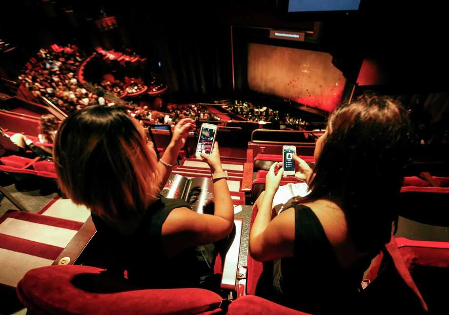 Reagan High School seniors Denise Morales, 19, left, and Lupita Herrera, 17, Snapchat themselves inside the Wortham Theater Center as they get ready to watch Houston Grand Opera's performance of Tosca. Photo: Karen Warren, Staff / © 2015 Houston Chronicle