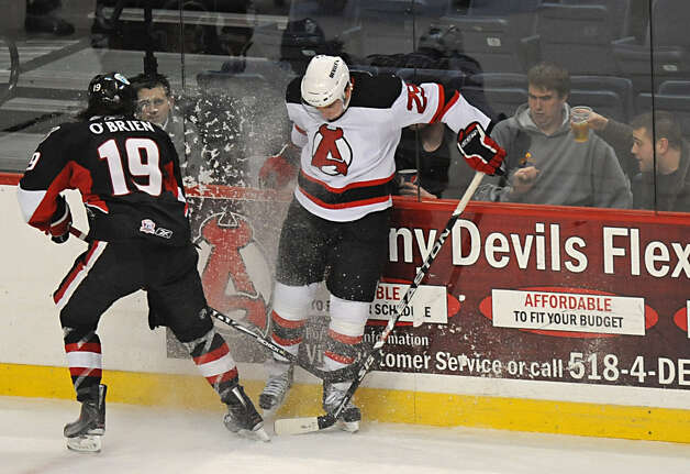 From left, Jim O'Brien, of the Binghamton Senators, battles for the puck against Matt Anderson, of the Albany Devils, during a hockey game at the Times Union Center in Albany, NY on January 19, 2011. (Lori Van Buren / Times Union) ORG XMIT: MER2015111215491519 Photo: Lori Van Buren / 00011283A