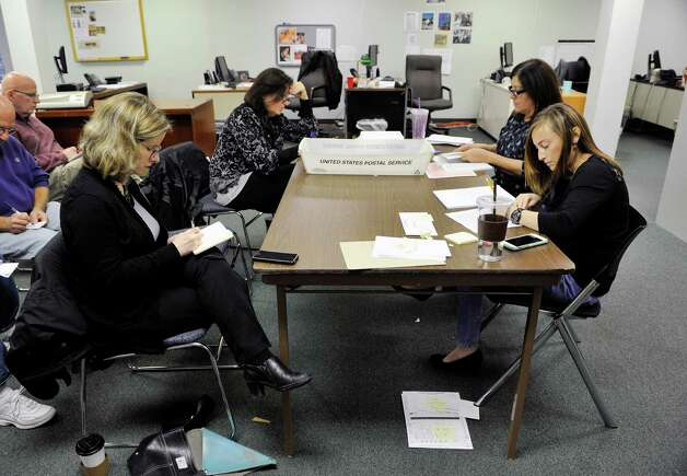Ellen Roach, foreground left, unofficial second place finisher for school board, and Sue Adler, background left, vice president of the Albany School Board, keep tally as Joslyn Strock, foreground right, education elections specialist, and Dorothy Crupe, senior election specialist, read out loud the votes on the Albany High School referendum during a count of absentee ballots at the Albany County Board of Elections on Thursday, Nov. 12, 2015, in Albany, N.Y.  Roach ran opposing the referendum.     (Paul Buckowski / Times Union) Photo: PAUL BUCKOWSKI / 00034220A