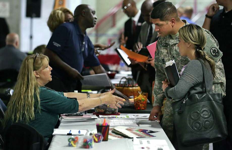 U.S. Army David Torres and his wife, Dennise Diaz, talk with Sherilyn Leone of Respite Care of San Antonio at a Texas Workforce Commission job fair. San Antonio logged 3.6 percent job growth in 2014 and 2015, said Keith Phillips, assistant vice president and senior economist for the San Antonio branch of the Dallas Fed. Photo: Bob Owen /San Antonio Express-News / San Antonio Express-News