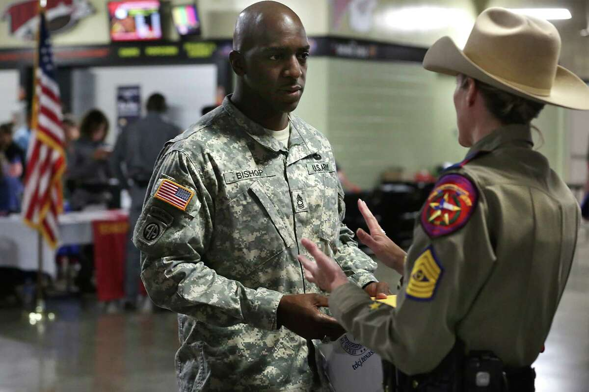 U.S. Army Master Sgt. Fredrick Bishop (left), who will retire next year, talks to Sgt. Arminda Henke of the Texas Department of Public Safety at a job fair earlier this month in San Antonio. October unemployment data shows that Texas is faring better than other U.S. energy states, likely ending the year with a net gain in jobs despite the oil bust, according to a Federal Reserve economist.