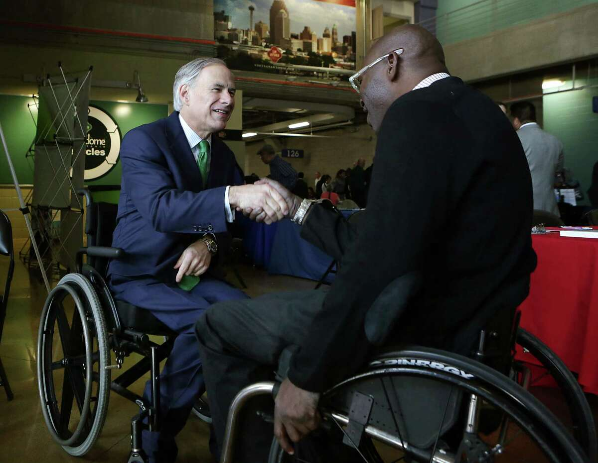 """Gov. Greg Abbott greets U.S. Army veteran William Neuls during a visit to the Texas Workforce Commission's """"Hiring Red, White and You"""" event at the Alamodome in San Antonio."""
