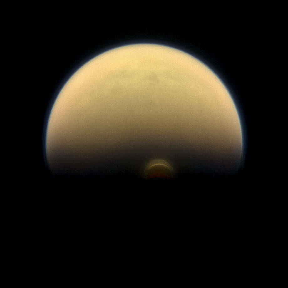 """As winter sets in at Titan's south pole, a cloud system called the south polar vortex (small, bright """"button"""") has been forming, as seen in this 2013 image. Credits: NASA/JPL-Caltech/Space Science Institute"""