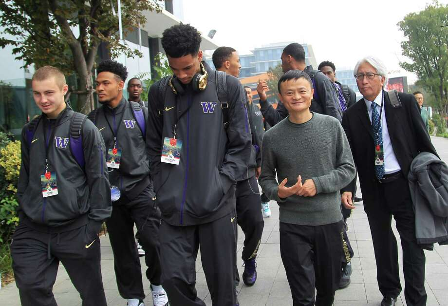 Jack Ma, second from right, executive chairman of the Alibaba Group, walks with players from the University of Washington mens' basketball team in Hangzhou in eastern China's Zhejiang province Tuesday, Nov. 10, 2015. On Saturday, two men's basketball teams from the University of Washington and the University of Texas will contest the first-ever regular season college basketball game in China, the first of perhaps many for U.S. university teams as they try to tap into a new market for their sports - and their schools - in the world's second-biggest economy. (AP Photo) Photo: Associated Press / AP
