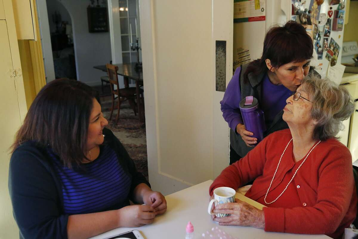 Susie Barrett, 54, left, kisses her mother Zoila Leon, 97, on the head as she leaves for work while Leon's caregiver Graciela Salas, 21, sits next to her at the kitchen table in Leon's home Nov. 12, 2015 in San Mateo, Calif. Leon was diagnosed with Alzheimer's in 2009 and the family has been employing Graciela Salas as Leon's in-home caregiver through CareLinx since August of this year. Salas says she likes CareLinx because of the pay and their flexibility.