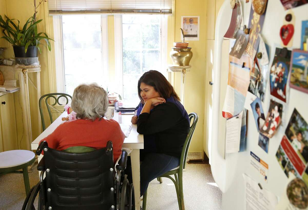 Zoila Leon, 97, left, flips through a magazine as she sits at the kitchen table with her caregiver Graciela Salas, 21, in Leon's home Nov. 12, 2015 in San Mateo, Calif. Leon was diagnosed with Alzheimer's in 2009 and the family has been employing Graciela Salas as Leon's in-home caregiver through CareLinx since August of this year. Salas says she likes CareLinx because of the pay and their flexibility.