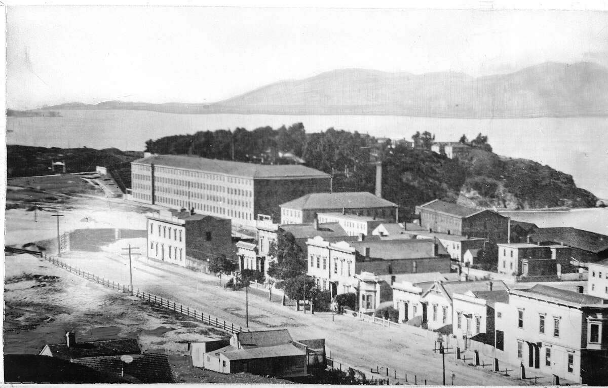 This photo taken in 1880 shows Bay Street between Hyde and Larkin. In the center foreground is the Montgomery House. The large building in the background is the Pioneer Woolen Mills and the arm of the bay is the west end of Aquatic Park.