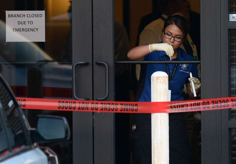 A Beaumont Police investigator swabs the handrail at Third Coast Bank after a robbery on Tuesday. According to police, a customer at the branch fired a handgun at the robber possibly striking him. Police are searching for the robbery suspect. Photo: Guiseppe Barranco, Photo Editor