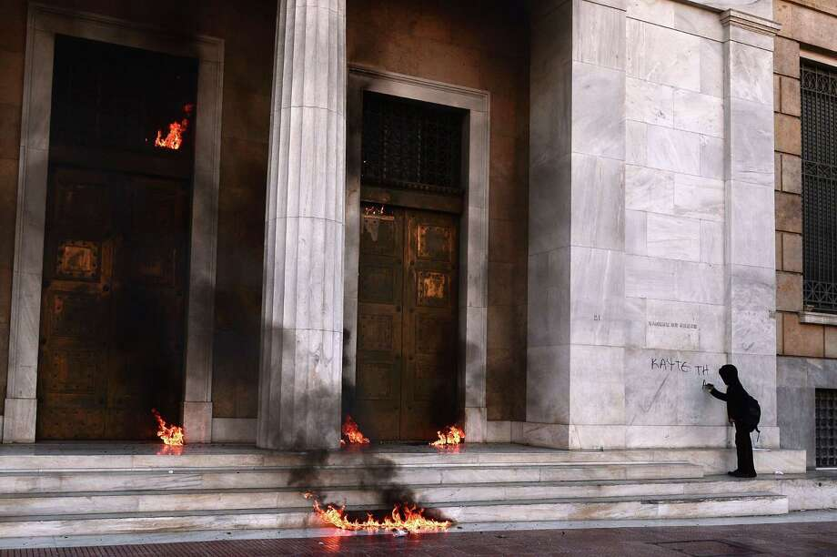 """A youth writes """"burn it"""" on the facade of the Bank of Greece headquarters amid Molotov cocktails thrown by demonstrators during a 24-hour general strike Thursday in Athens. Around 20,000 people protested new austerity measures. Photo: LOUISA GOULIAMAKI, Stringer / AFP"""