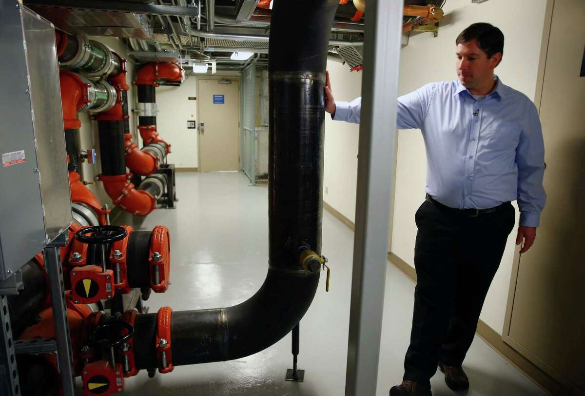 """McKinstry Project Manager Adam Myers explains the workings of a new """"district energy"""" system in the Westin Building in Downtown Seattle, Thursday, Nov. 12, 2015. The system will recycle waste heat from the many Internet servers housed in the building and pipe it across the street to heat Amazon's newest buildings."""