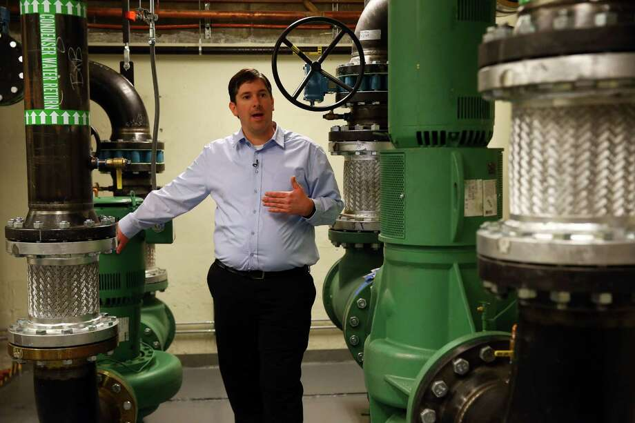 "McKinstry Project Manager Adam Myers explains the workings of a new ""district energy"" system in the Westin Building in Downtown Seattle, Thursday, Nov. 12, 2015.  The system will recycle waste heat from the many Internet servers housed in the building and pipe it across the street to heat Amazon's newest buildings. Photo: GENNA MARTIN, SEATTLEPI.COM / SEATTLEPI.COM"