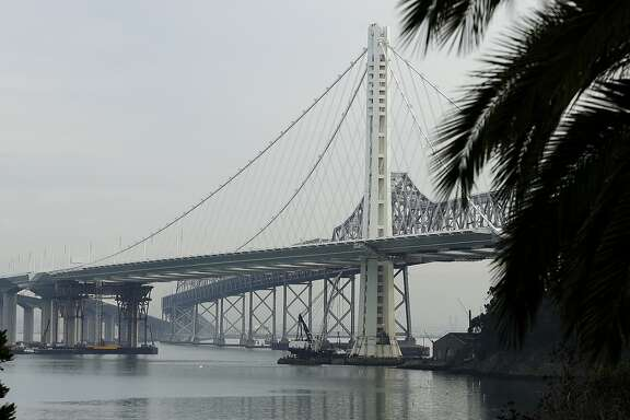 Work continues on the new eastern span of the San Francisco Oakland Bay Bridge, foreground, Tuesday, Jan. 7, 2014, in San Francisco. The original span, background, will be dismantled. (AP Photo/Ben Margot)