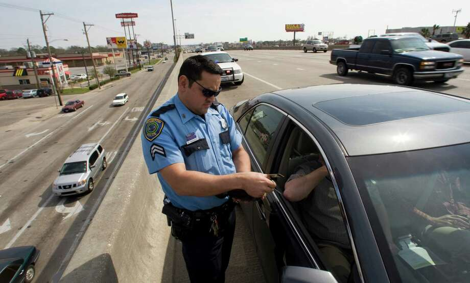 Houston Police senior officer Robert Manzanales writes a citation as he enforces the Move Over Law on the Gulf Freeway Monday, Feb. 16, 2009, in Houston.  Photo: Brett Coomer, Staff / Houston Chronicle