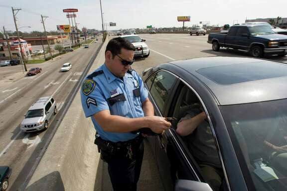 Houston Police senior officer Robert Manzanales (cq) writes a citation as he enforces the Move Over Law on the Gulf Freeway Monday, Feb. 16, 2009, in Houston. When approaching a stationary emergency vehicle, drivers are required by law to vacate the lane closest to the emergency vehicle or slow to 20 miles per hour below posted speed. ( Brett Coomer / Chronicle )