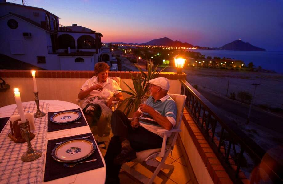 Dorothy and Jack Biely dining by candlelight on their balcony overlooking the Sea of Cortez, a retired couple from California living the affordable good life in one of a handful of Mexican towns attracting American retirees.  
