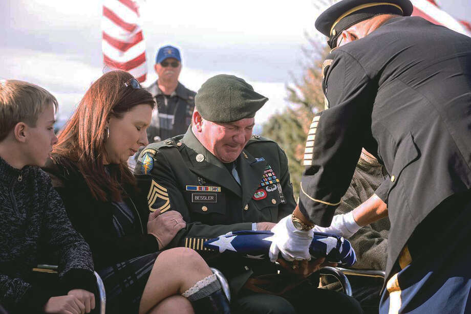 Sgt. 1st Class Matthew Bessler  reacts after receiving an American flag during a memorial service for Michael, the dog that served with him in Iraq.   Photo: Carla Wensky, MBR / The Powell Tribune
