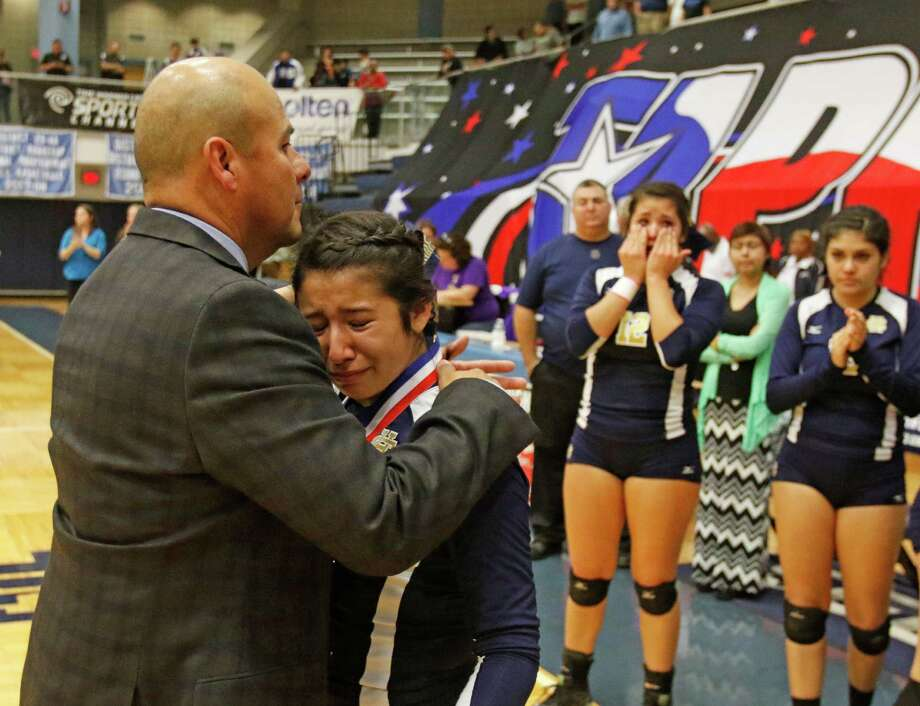 Holy Cross head coach Ruben Calderon consoles Autumn Lopez after  the TAPPS 4A state semifinal volleyball match. Photo: Ron Cortes /For The San Antonio Express-News / San Antonio Express-News