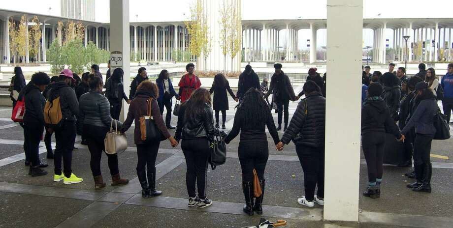 University at Albany students hold hands in prayer following a solidarity demonstration Thursday, Nov. 12, 2015, at the University at Albany campus in Albany, N.Y. Campuses around the nation participated in similar rallies following the racially charged events at the University of Missouri. (Madeline St. Amour / Albany Student Press)