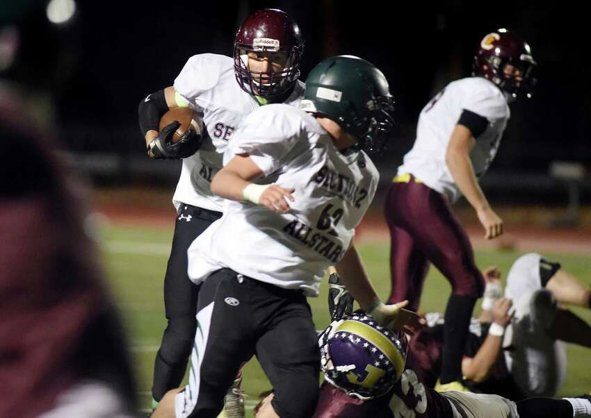 Colonie's Dan Kehrer, left, gets protection from Schalmont's Sean Coons, center, as they play on the South Team together against the North Team during the Exceptional Seniors football game on Thursday, Nov. 12, 2015, at Shenendehowa in Clifton Park, N.Y. (Cindy Schultz / Times Union)