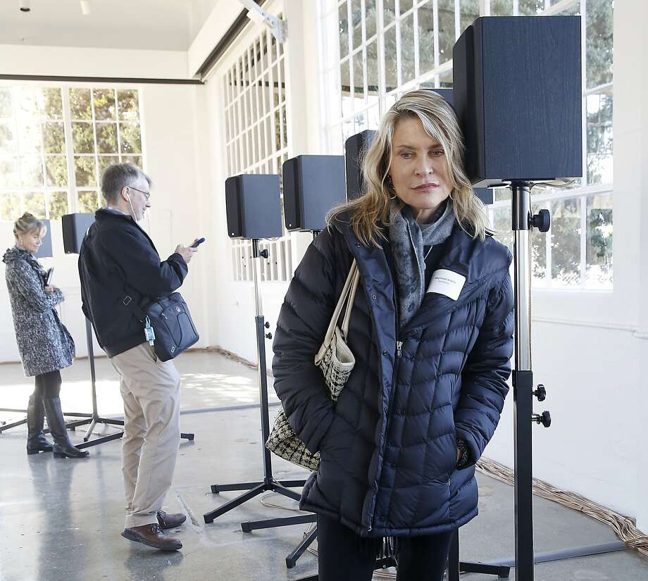 "Juxtapoz publisher Gwynned Vitello listens to sound artist Janet Cardiff's installation ""Forty-Part Motet"", using speakers to resonate a forty part choral piece by composer Thomas Tallis at Fort Mason in San Francisco, California, on Thursday, November 12, 2015. Photo: Liz Hafalia, The Chronicle"