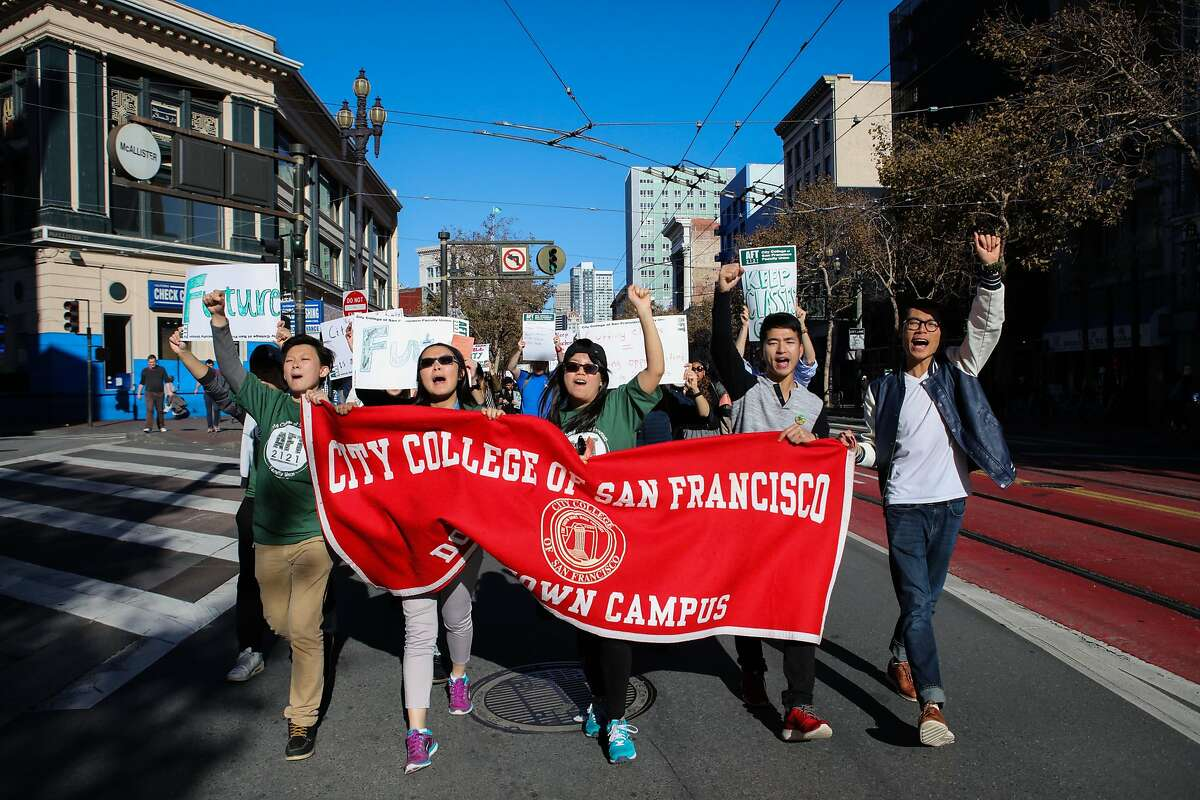(l-r) Gary Liang, Esther Wu, Jenny Chen, Dan Zhang, and Zhen Ye Pan, all CCSF students, march down Market Street in protest of the anticipated budget cuts at CCSF, in San Francisco, California on Thursday, November 12, 2015.
