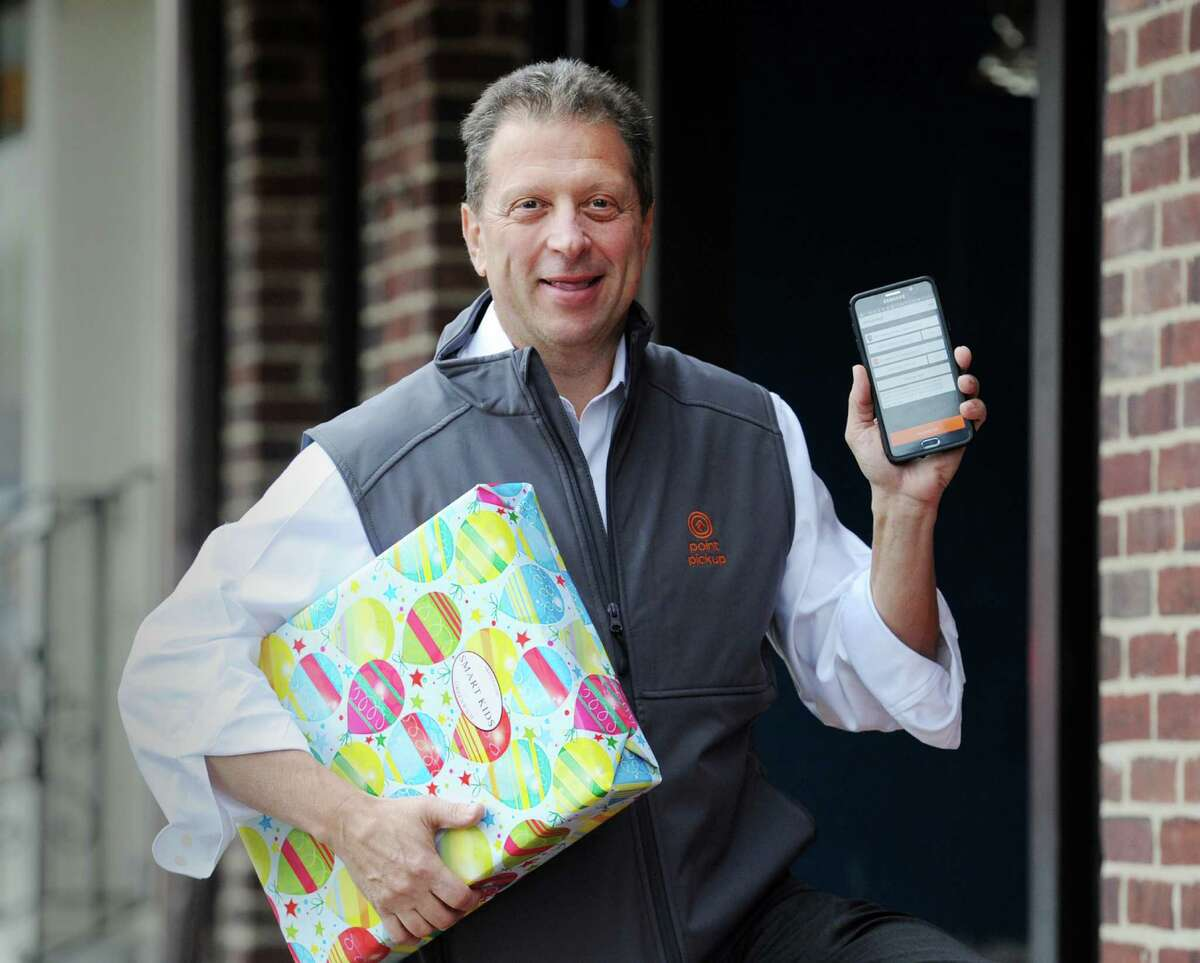 Founder and CEO of Point PickUp Technologies, Inc., Tom Fiorita, holds up his mobile device displaying his company's app along with a package outside the Smart Kids Toy store on East Elm Street in Greenwich.
