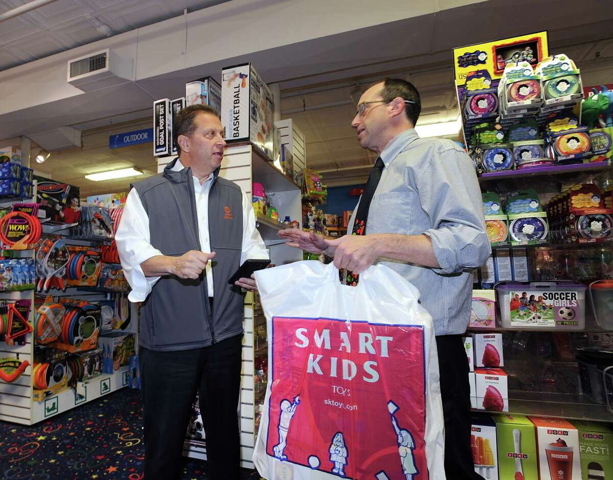 Fiorita, speaks with Andrew Lev, the manager of the Smart Kids Toy store on East Elm Street in Greenwich , on Thursday.