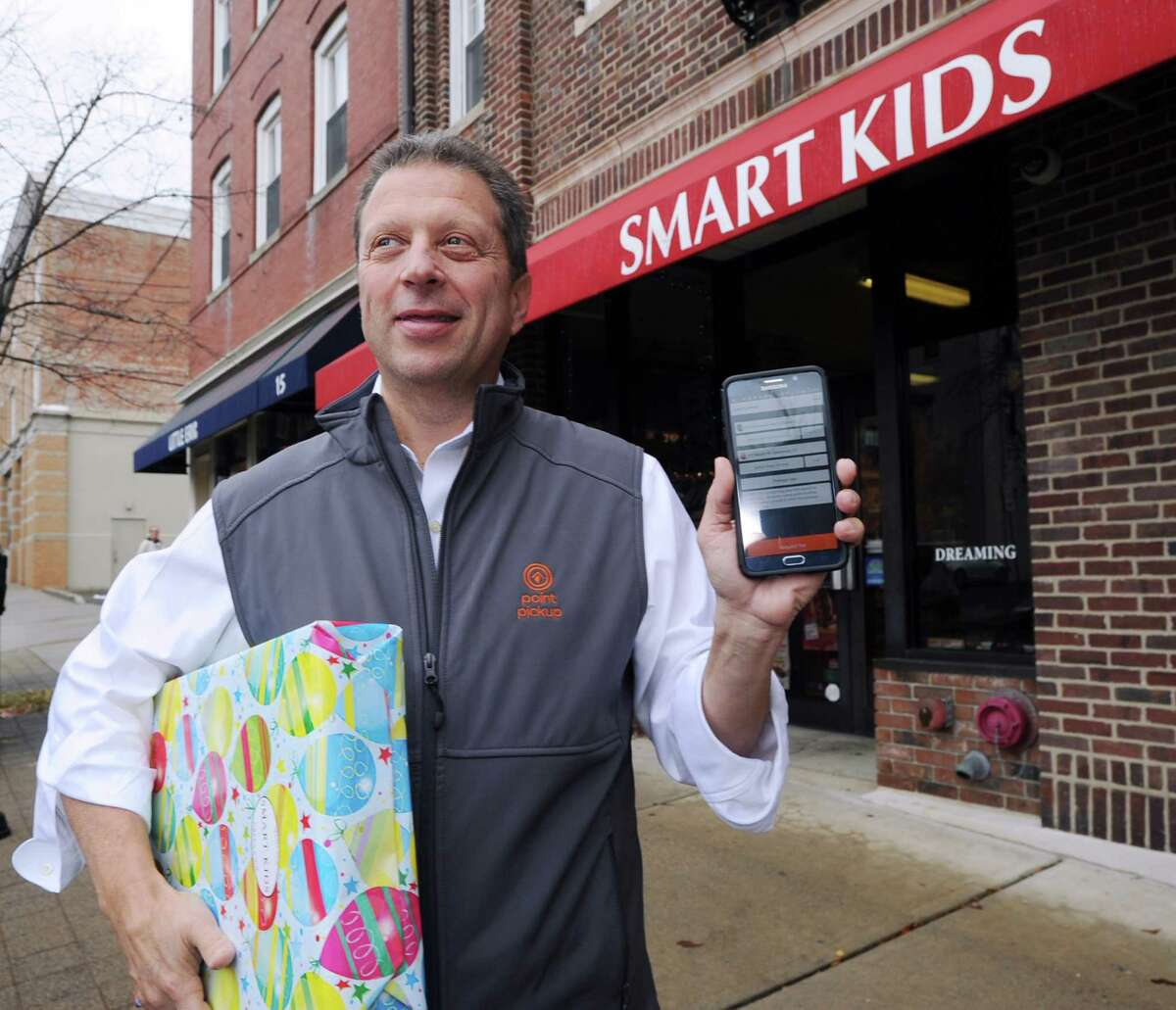 """Founder & CEO of Point Pick-Up Technologies, Inc., Tom Fiorita, holds up his mobile device displaying his company's app along with a package outside the Smart Kids Toy store on East Elm Street in Greenwich , Conn., Thursday, Nov. 12, 2015. Fiorita's tech start-up is a facilitator for local same-day delivery of packages. According to the company's website, pointpuckup.com, """"connects folks that need stuff delivered with Pickup Partners who do the delivering."""""""